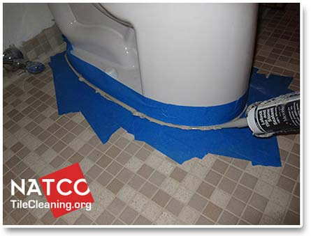applying caulk around toilet