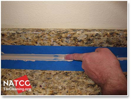 smoothing caulk with finger